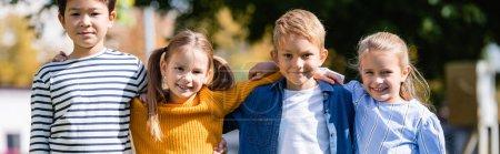 Photo pour Enfants multiethniques joyeux étreignant tout en regardant la caméra à l'extérieur, bannière - image libre de droit