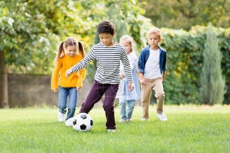 Photo pour Asiatique garçon jouer football près amis sur flou fond dans parc - image libre de droit