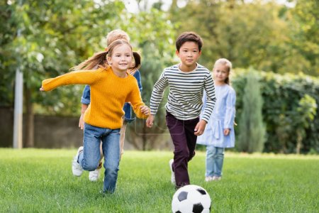 Cheerful multiethnic kids playing football near friends on blurred background in park