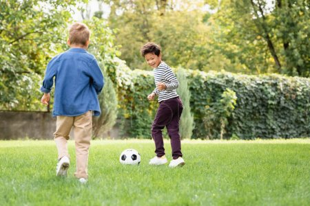 Smiling asian boy playing football near friend on grass in park