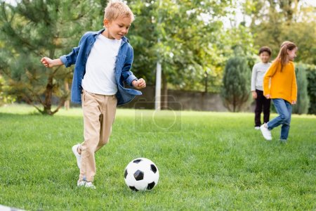 Smiling boy playing football near friends on blurred background in park