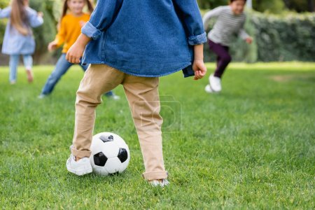 Photo for Boy playing football with friends on blurred background on lawn - Royalty Free Image