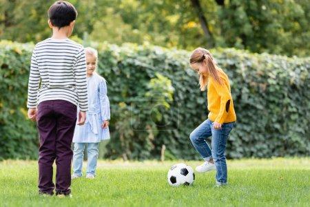 Photo pour Souriant fille jouer au football près des amis sur pelouse herbeuse - image libre de droit
