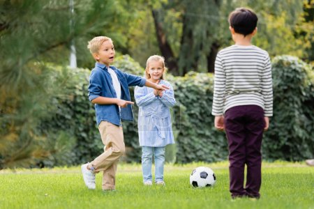Photo for Excited boy pointing with fingers near football and friends in park - Royalty Free Image