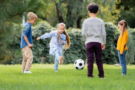 Photo pour Fille jouer au football avec des amis sur le premier plan flou dans le parc - image libre de droit