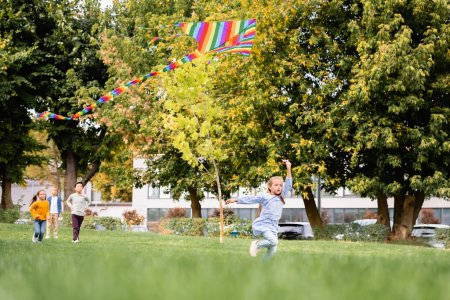 Photo for Kid running with flying kite near friends on blurred background on meadow in park - Royalty Free Image