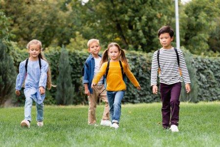 Photo pour Écoliers multiculturels marchant avec des sacs à dos sur la pelouse dans le parc - image libre de droit
