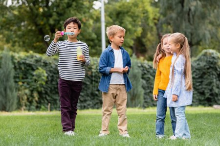 Photo for Asian boy blowing soap bubbles while standing near smiling friends on grassy lawn - Royalty Free Image