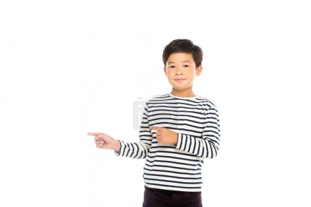 Asian boy looking at camera while pointing with fingers isolated on white