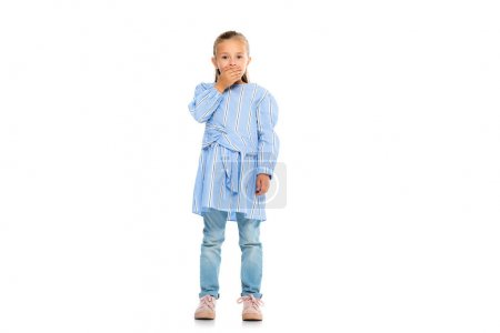 Excited child covering mouth with hand while looking at camera on white background