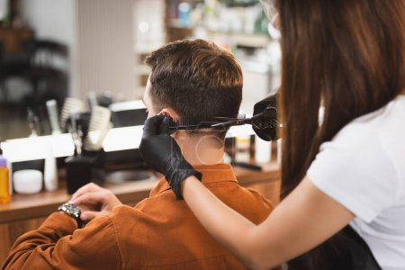 man looking at wristwatch while hairstylist on blurred foreground cutting his hair