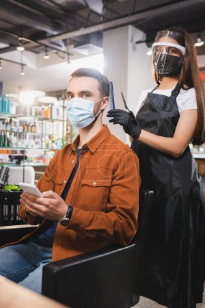 hairdresser in protective equipment looking at camera near client holding smartphone
