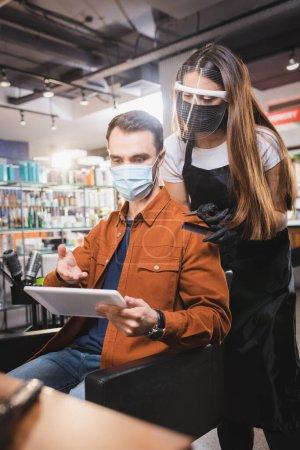 Mann in medizinischer Maske zeigt mit der Hand auf Tablet in der Nähe von Friseur in Schutzausrüstung