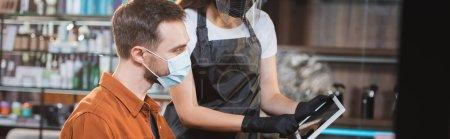 Friseur in Schutzausrüstung zeigt dem Mann in medizinischer Maske das digitale Tablet, Banner
