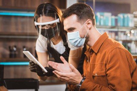 Friseur im Gesichtsschutz hält digitales Tablet in der Nähe des Kunden in medizinischer Maske und zeigt mit den Händen