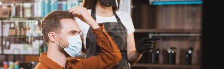 Photo pour Homme en masque médical touchant ses cheveux près du coiffeur dans un équipement de protection pointant du doigt, bannière - image libre de droit