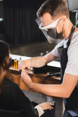 barber in face shield cutting hair of woman in medical mask