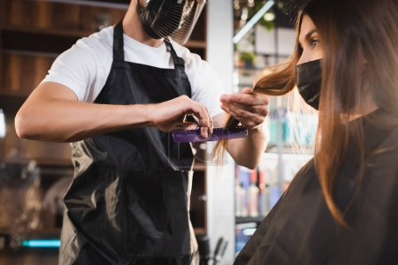 barber in apron and face shield cutting hair of client in medical mask