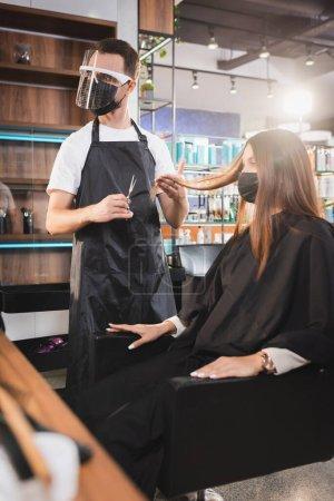 Photo pour Coiffeur dans le bouclier facial tenant des ciseaux et touchant les cheveux du client, avant-plan flou - image libre de droit