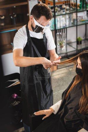 Photo pour Coiffeur dans le bouclier facial et tablier coupe les cheveux de la femme dans le masque médical, avant-plan flou - image libre de droit