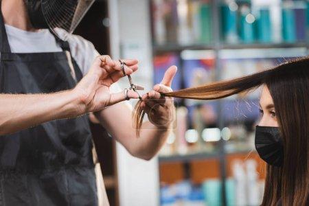 Photo pour Coiffeur en équipement de protection couper les cheveux de la femme dans le masque médical - image libre de droit