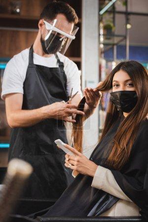 Photo pour Femme en masque médical à l'aide d'un smartphone tandis que le coiffeur dans le bouclier facial couper ses cheveux, flou premier plan - image libre de droit