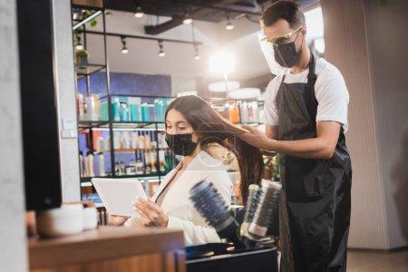 Photo pour Coiffeur dans le bouclier facial et tablier regardant les cheveux de la femme tenant tablette numérique - image libre de droit