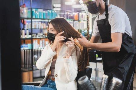 Photo pour Coiffeur en tablier et écran facial touchant les cheveux de la femme en masque médical, avant-plan flou - image libre de droit