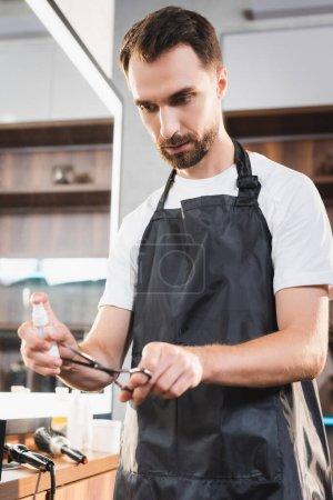 Photo pour Jeune coiffeur barbu désinfectant ciseaux avec désinfectant - image libre de droit