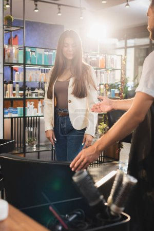 Photo pour Coiffeur montrant geste de bienvenue à la femme tout en se tenant près du fauteuil, avant-plan flou - image libre de droit