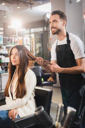 Photo pour Coiffeur souriant en tablier touchant les cheveux de la jeune femme, premier plan flou - image libre de droit