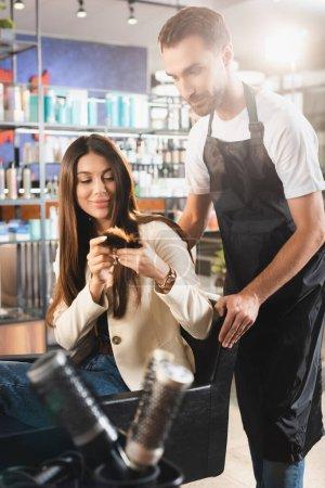 Photo pour Jeune femme montrant des pointes de cheveux au barbier barbu dans le tablier - image libre de droit