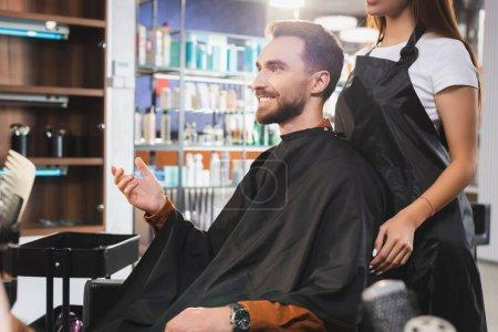 Photo pour Coiffeur dans tablier debout près client heureux pointant avec la main - image libre de droit