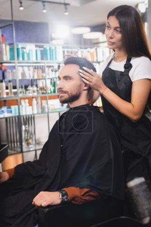Photo pour Barbier dans tablier touchant les cheveux du jeune homme barbu dans le salon de coiffure, avant-plan flou - image libre de droit
