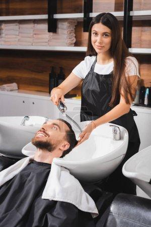 Photo pour Jeune coiffeur dans tablier regardant la caméra tout en lavant les cheveux du client heureux - image libre de droit