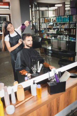 Photo pour Miroir reflet de coiffeur séchage des cheveux du client avec des bouteilles cosmétiques sur le premier plan flou - image libre de droit
