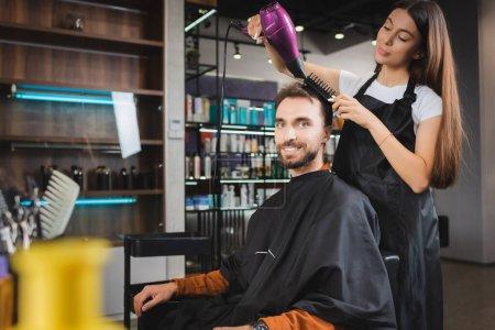 Photo pour Homme barbu souriant à la caméra tandis que le coiffeur sèche ses cheveux, avant-plan flou - image libre de droit