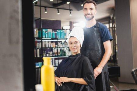 Photo pour Coiffeur joyeux et femme souriante avec les cheveux enveloppés dans la serviette en regardant la caméra, avant-plan flou - image libre de droit