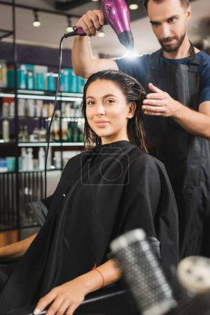 Photo pour Femme souriante regardant caméra tandis que jeune coiffeur séchant ses cheveux - image libre de droit