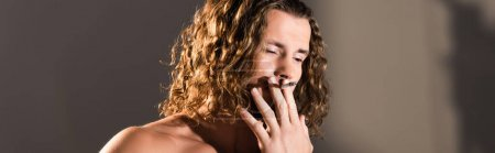 sexy shirtless man with long hair smoking on dark background, banner