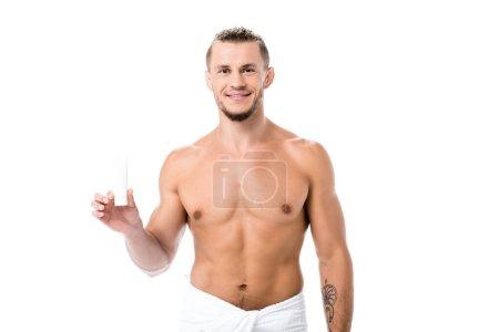 Photo pour Homme torse nu sexy souriant en serviette avec crème pour les mains isolée sur blanc - image libre de droit