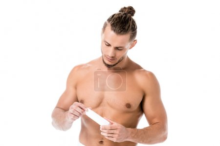 sexy shirtless man in towel with hand cream isolated on white