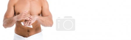 cropped view of sexy shirtless man in towel applying hand cream isolated on white, banner