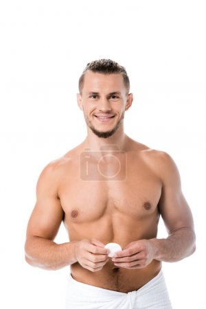 smiling sexy shirtless man in towel with cotton pad isolated on white