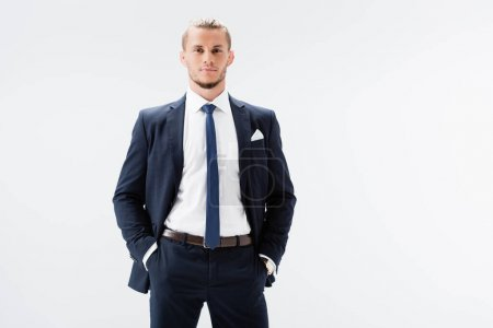 young businessman in suit posing with hands in pockets isolated on white