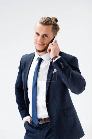 Photo pour Souriant jeune homme d'affaires en costume parler sur smartphone isolé sur blanc - image libre de droit