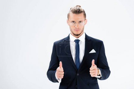 young businessman in suit and glasses showing thumbs up isolated on white