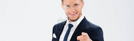 happy young businessman in suit and glasses pointing at camera isolated on white, banner