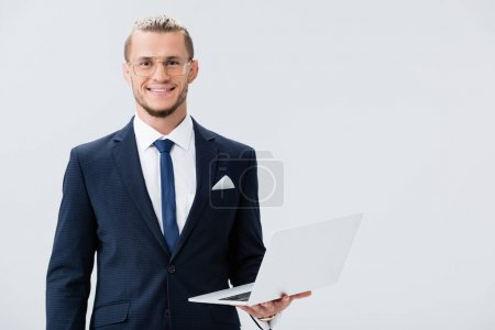 Photo for Smiling young businessman in suit and glasses with laptop isolated on white - Royalty Free Image
