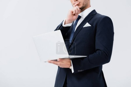 cropped view of pensive young businessman in suit with laptop isolated on white
